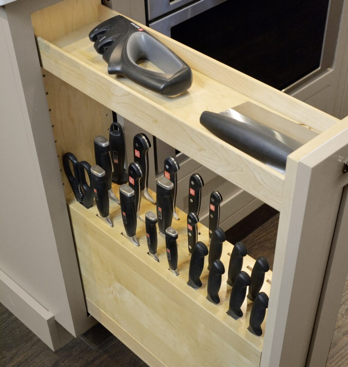 A Knife Block Pull-Out Cabinet using the top tier for misc. food preparation tools.