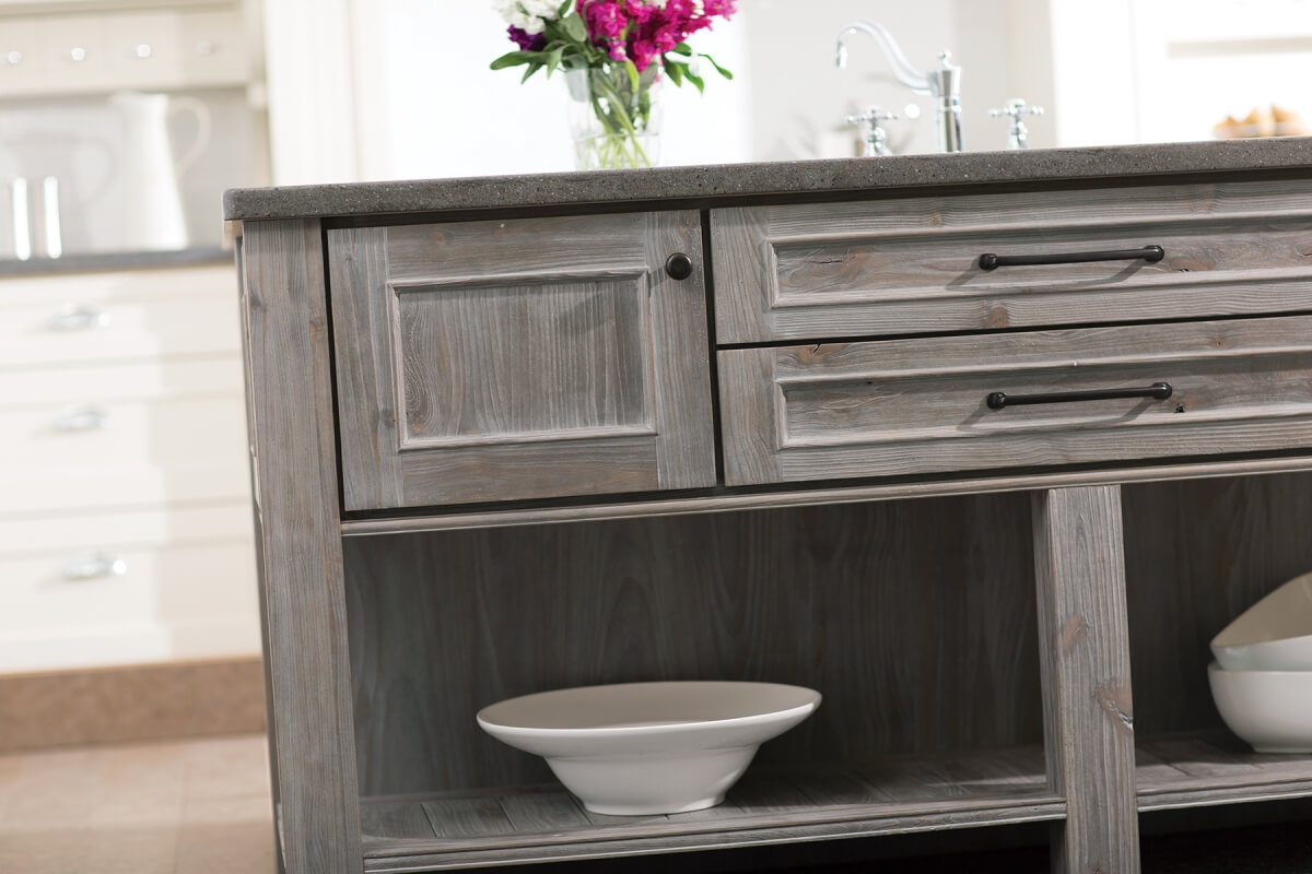 A kitchen island with a weathered wood finish with a gray stain and a furniture-style look.