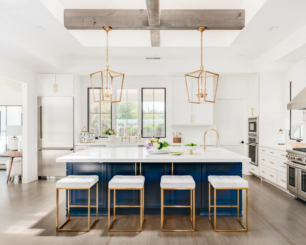 Trend setting navy blue and white kitchen with gold hadware and large-scaled pendant lights.