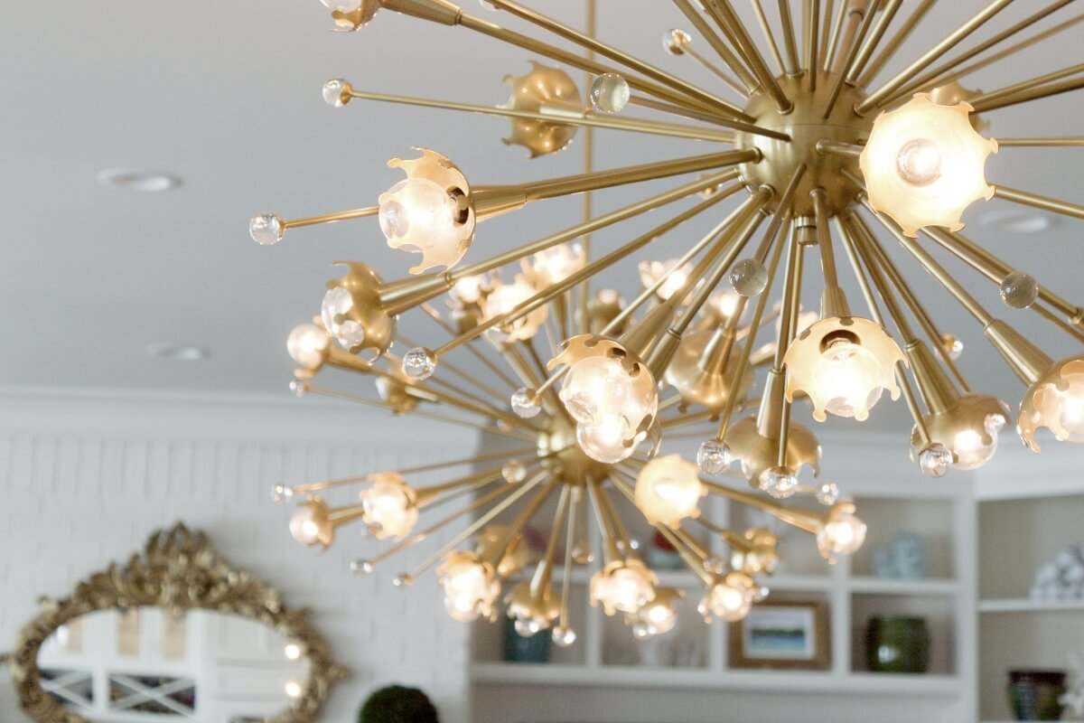 Gold Pendant Lights in a beautiful modern kitchen design with white painted cabinets.