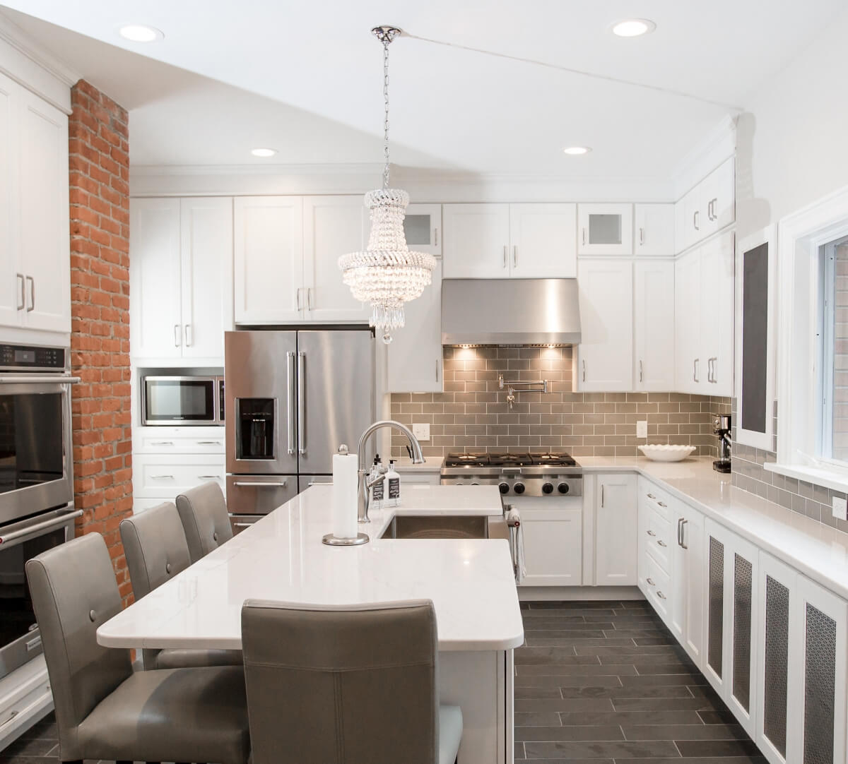 A white on white kitchen with Dura Supreme cabinetry and a large chandalier over the kitchen island.