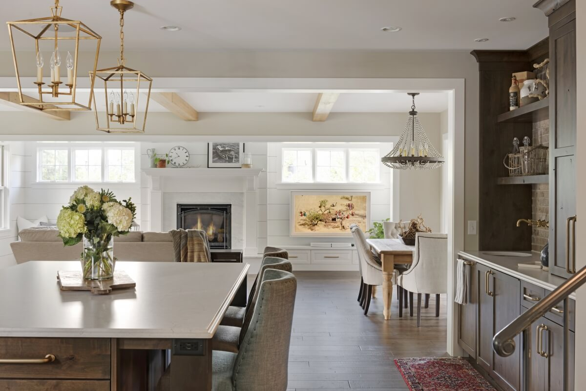 This kitchen features two grand sizes pendants over the kitchen island and 1 large chandelier over the dining room table to define the 2 spaces in the open floor plan. Dura Supreme design by Studio M Kitchen & Bath.