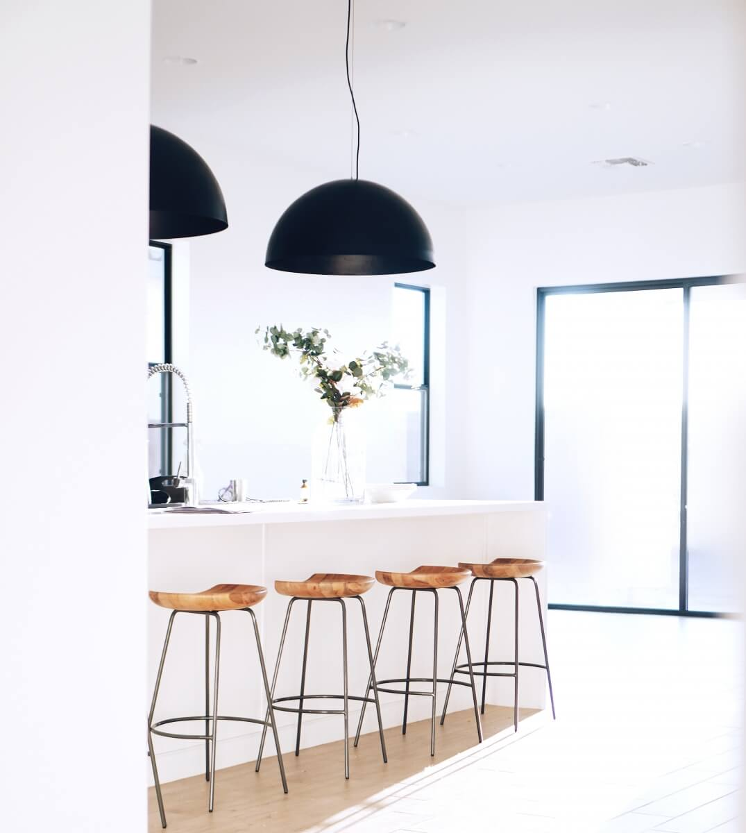 An example of a kitchen design trend. Two overzied black light shades on pendant lights over a kitchen island. Kitchen design trends to consider.