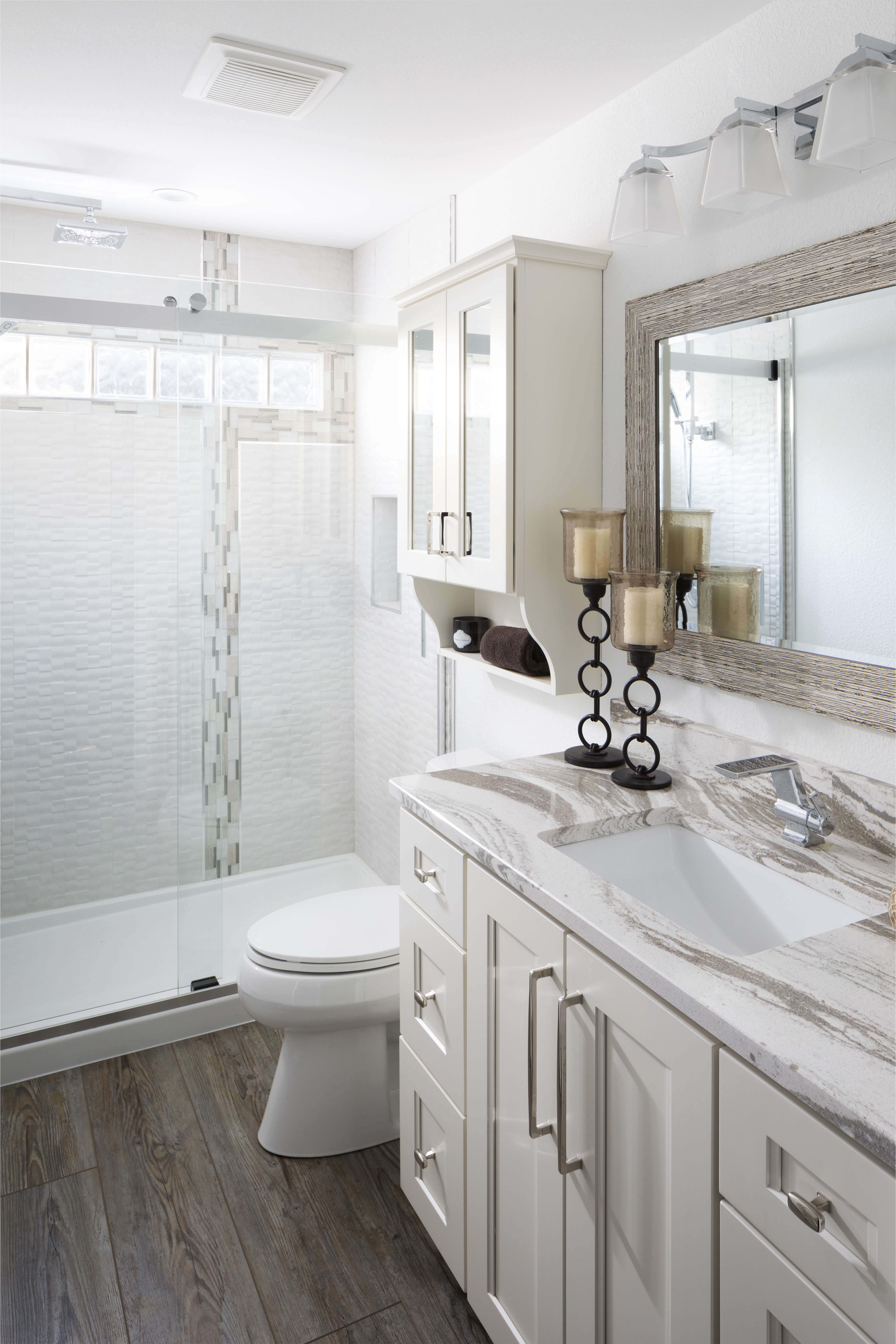 A newly remodeled bathroom with whote painted cabinets and mirrored cabinet doors.