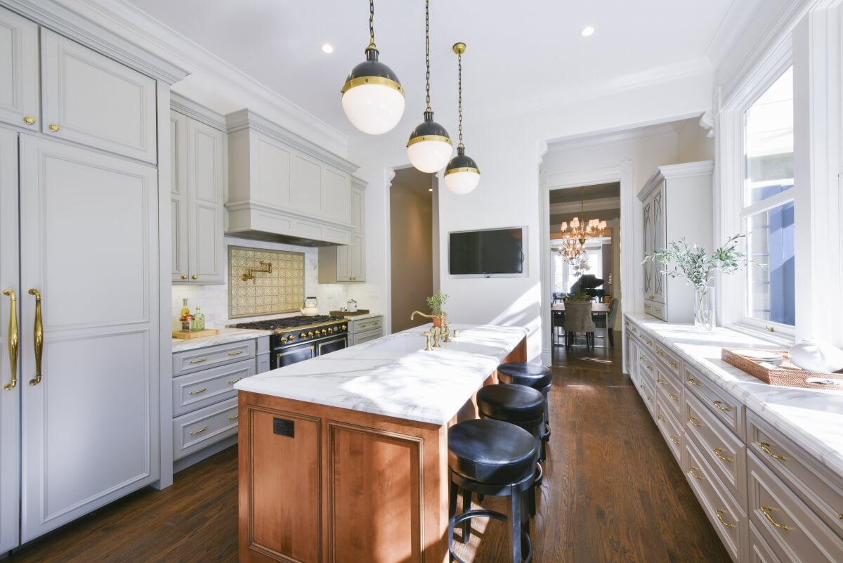 Counter height bar stool seating at a kitchen island with a kitchen island sink.