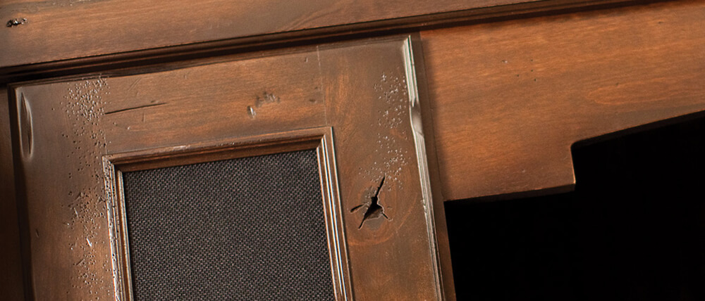 A close up of distressed stained cabinets with a patina finish from Dura Supreme Cabinetry.