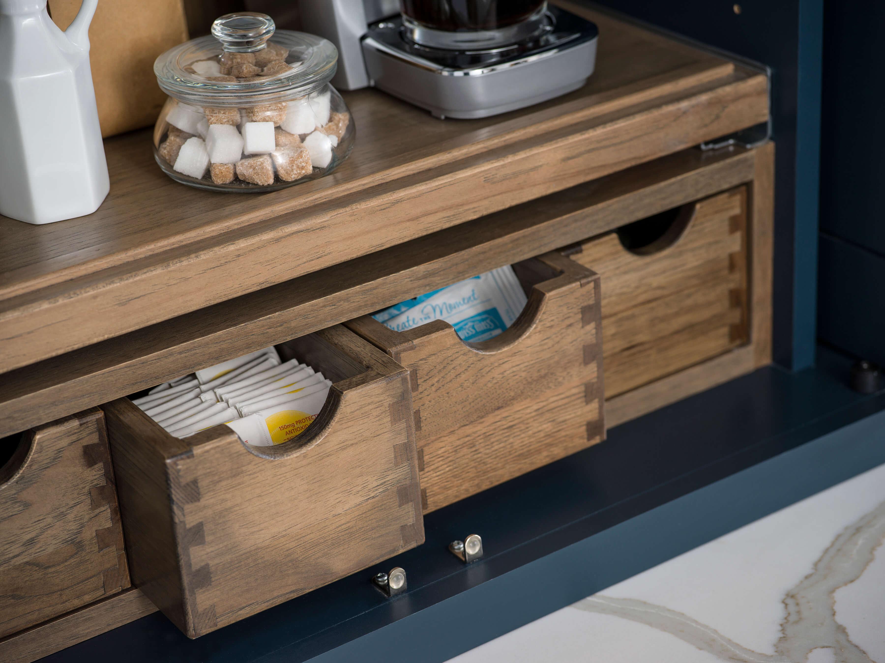 A close up of Apothecary Drawers inside a Beverage Center Larder from Dura Supreme Cabinetry
