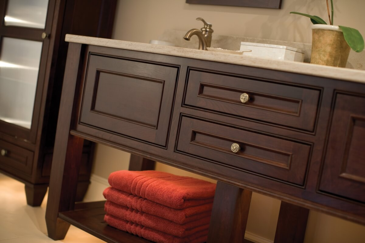 A bathroom vanity by Dura Supreme Cabinetry with an open shelf by the floor for storing towels and other everyday items.