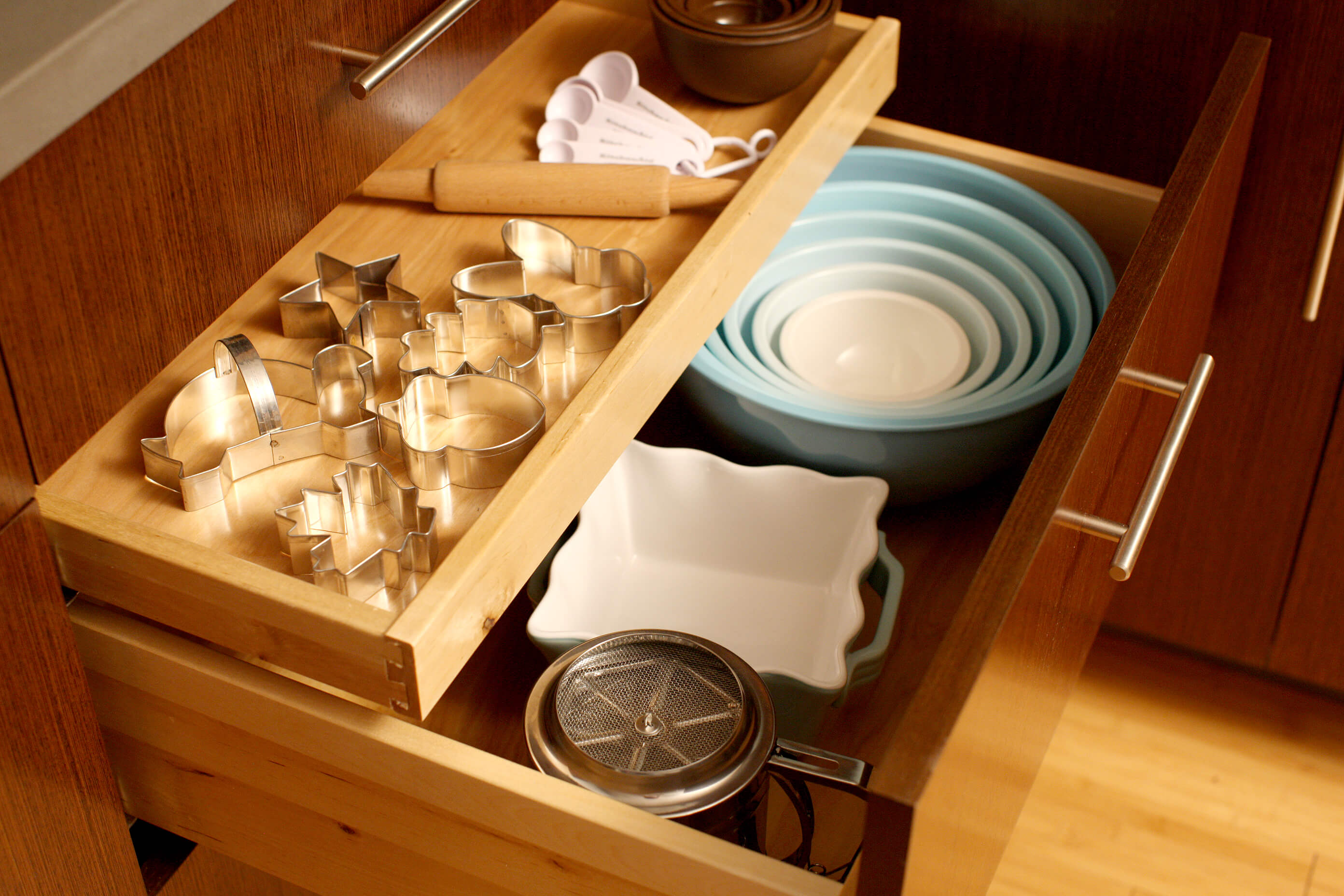 Keep all your baking supplies in one spot by using a deep drawer for mixing bowls with a small roll-out tray for your cookie cutters and misc. baking tools.