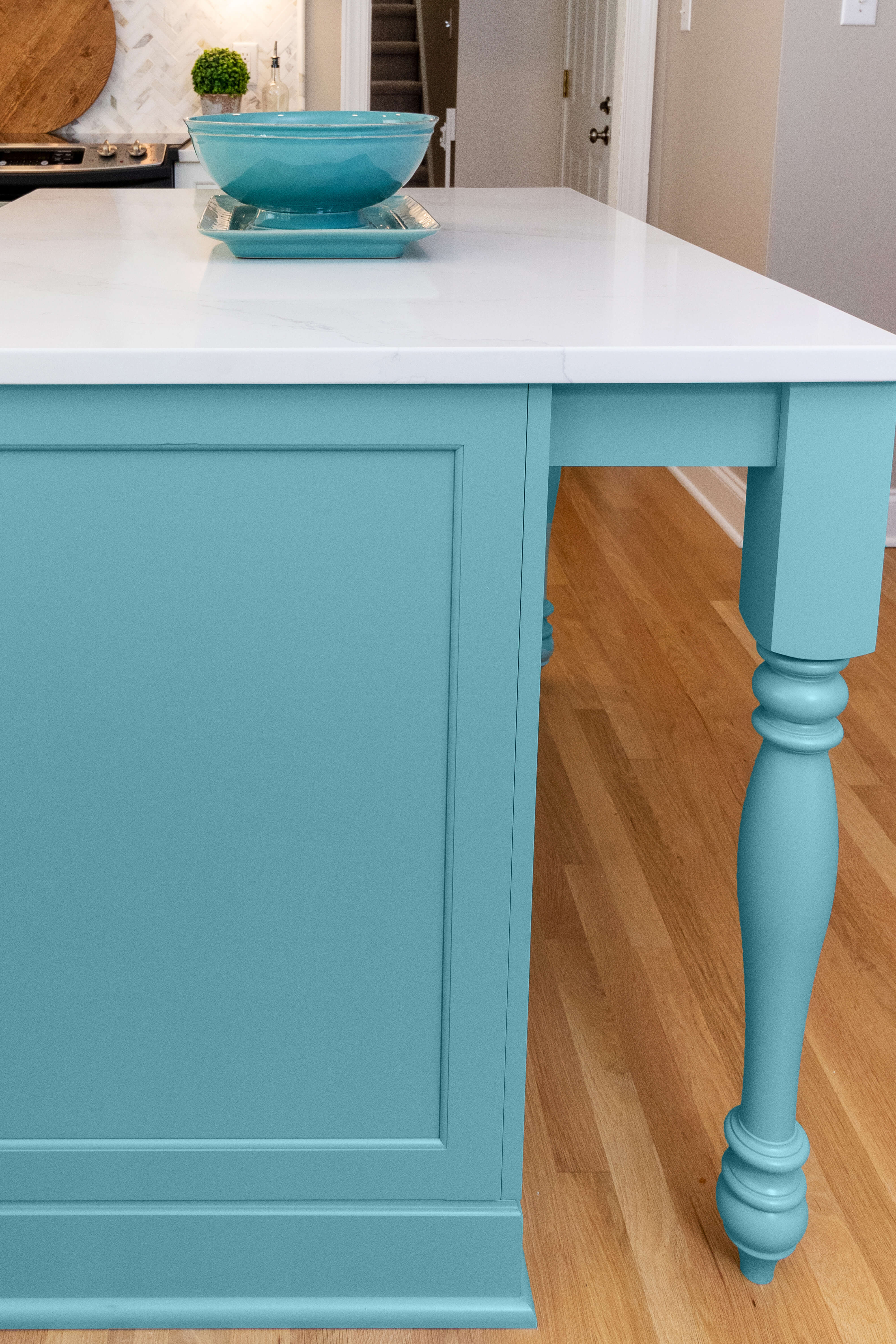 A sky blue kitchen island with turned post table legs. Painted kitchen island cabinets from Dura Supreme Cabinetry.